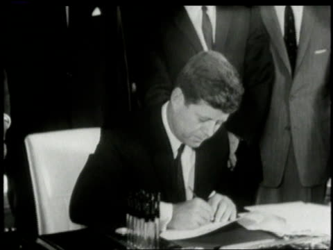White House staff members look on as John F Kennedy dips pen into ink and signs bill / Washington DC United States