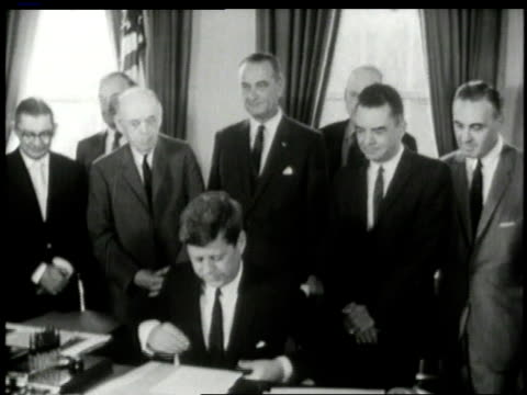 white house staff members look on as john f kennedy signs piece of paper / washington d.c., united states - john f. kennedy us president stock videos & royalty-free footage