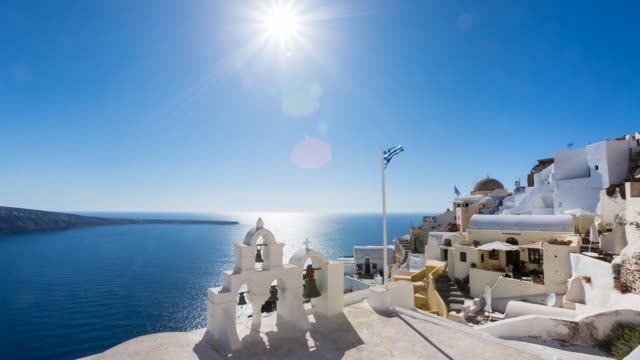 ws white houses clinging to cliff top overlooking mediterranean sea - サントリーニ島点の映像素材/bロール