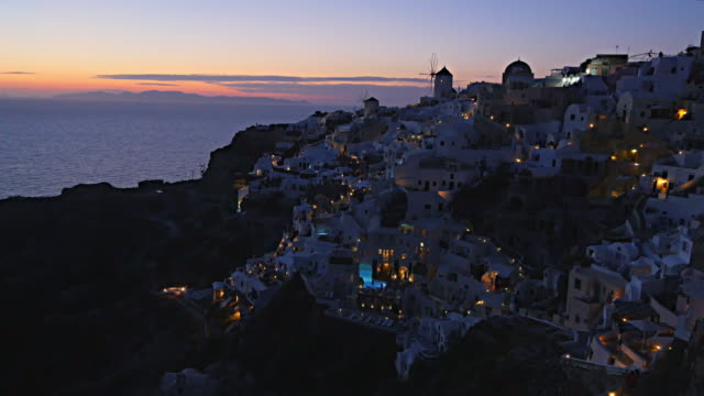 vídeos de stock, filmes e b-roll de ws white houses clinging to cliff top overlooking mediterranean sea - oia santorini