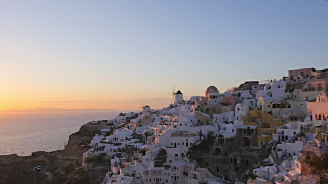 ws white houses clinging to cliff top overlooking mediterranean sea - insel santorin stock-videos und b-roll-filmmaterial