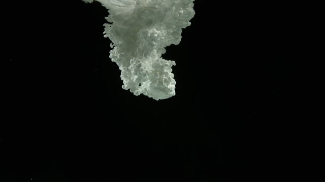 White Ink entering Water against Black Background, Slow motion 4K