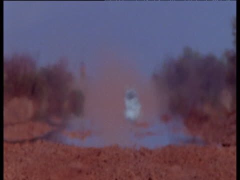 white jeep drives towards camera in australian desert though heat haze - heat haze stock videos & royalty-free footage