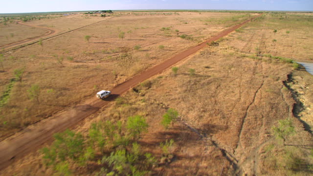 WS TS AERIAL White jeep on dusty road with dried grass landscape / Karumba, Queensland, Australia