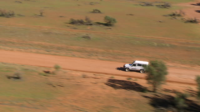 vídeos de stock e filmes b-roll de ms ts aerial white jeep running on dusty road landscape / pooncarie, new south wales, australia - jeep