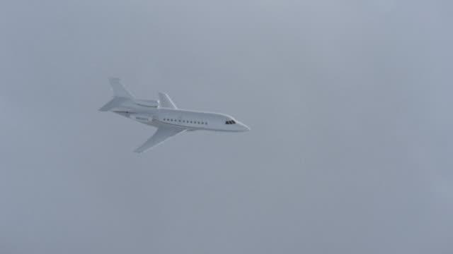 a white jet flies through heavy cloud cover. - flugzeug in der luft stock-videos und b-roll-filmmaterial
