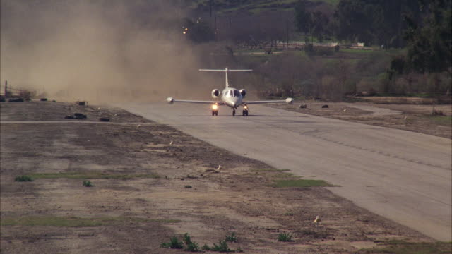 MS TS White lear company jet with brown stripe and black under belly  taking off from small desolate airport.