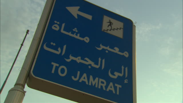 White lettering on a blue sign announces in English and Arabic the way to Jamrat.