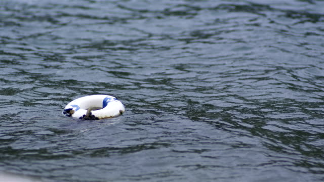 A White Lifebuoy Into The Water And Floats On It