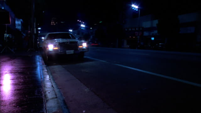 white limousine pulls up on sidewalk of hollywood boulevard at night, los angeles, california, usa available in hd. - リムジン点の映像素材/bロール