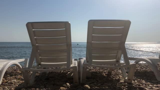 vídeos de stock, filmes e b-roll de espreguiçadeiras branco em uma linda praia tropical em büyükada istambul - espreguiçadeira