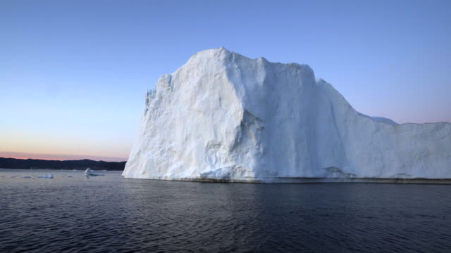 white majestic iceberg on disko bay against blue sky during sunset - inlet stock videos & royalty-free footage
