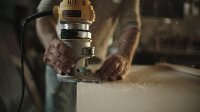 white male carpenter in his forties routers a piece of wood - manual worker stock videos & royalty-free footage