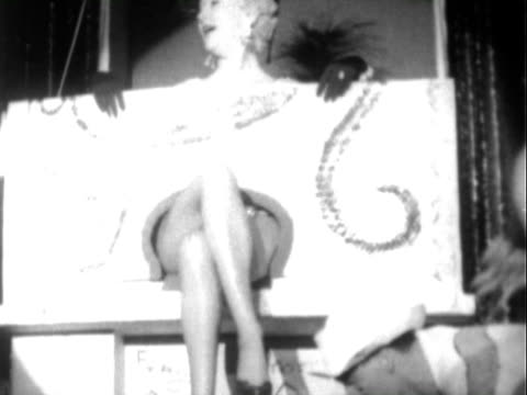 white male dancers in matching baremidriff outfits dancing wheeling cart and boxes onto stage / famous legs of betty grable protrude / betty grable... - burlesque stock videos & royalty-free footage