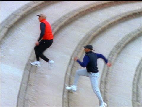 pan white man in vest + black man running up stadium steps / red rocks amphitheater - red rocks stock-videos und b-roll-filmmaterial