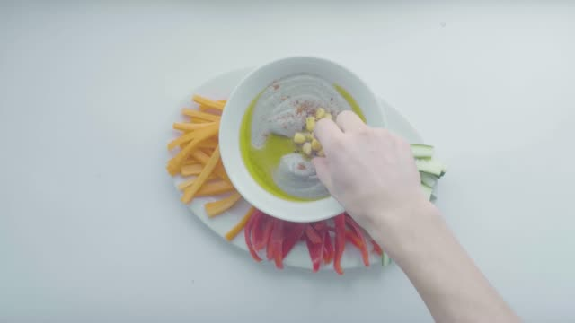vídeos y material grabado en eventos de stock de white man's hand holds a chopped vegetable from oval white plate with chickpea hummus sauce in the middle, cucumber, yellow and red peppers - decoración artículos domésticos
