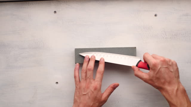 white man's hand sharpening a kitchen knife on a rectangular stone - kitchenware shop stock videos & royalty-free footage