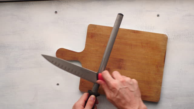 vídeos de stock, filmes e b-roll de white man's hand sharpening a kitchen knife with a honing steel over a cutting board in a white and rustic table - afiado