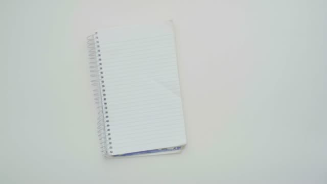 white man's hands writing in a notebook with a pencil on a white background table - pencil isolated stock videos & royalty-free footage