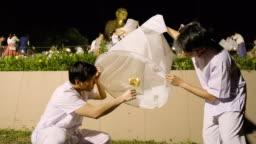 White Meditation clothing men lighting a Sky Lantern