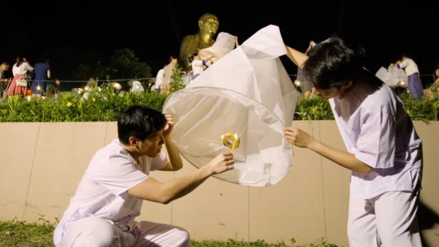 vídeos de stock e filmes b-roll de white meditation clothing men lighting a sky lantern - lanterna de papel