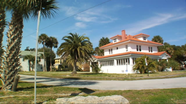 White Mediterranean style beach house w/ orange roof against blue sky cabbage palm trees surrounding home Summer home beachfront property timeshare...