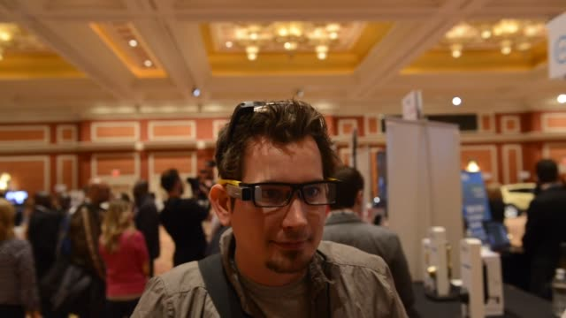 White middle aged male waring high tech glasses looks up and tilts head down at Consumer Electronics Show in Las Vegas NV Close up on white middle...