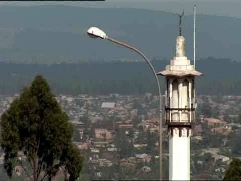 ws white minaret with crescent motif stands high above rooftops of nyamiramb / nyamirambo, kigali, rwanda - キガリ点の映像素材/bロール