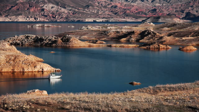 A white motorboat cruising through a channel in Lake Mead