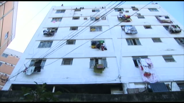 White multistory multiwindow tenement building with clothing and goods hanging from windows / Brazil