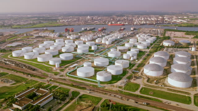 aerial white oil refinery storage tanks on the bank of a river in houston, tx - oil industry stock videos & royalty-free footage