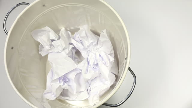 White paper falling into the garbage can