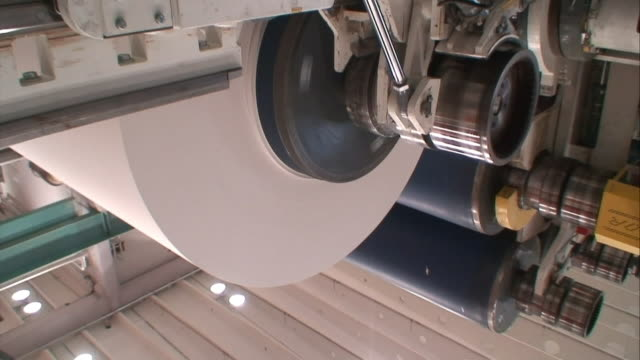 white paper spins around a roller at a paper mill. - paper mill stock videos and b-roll footage