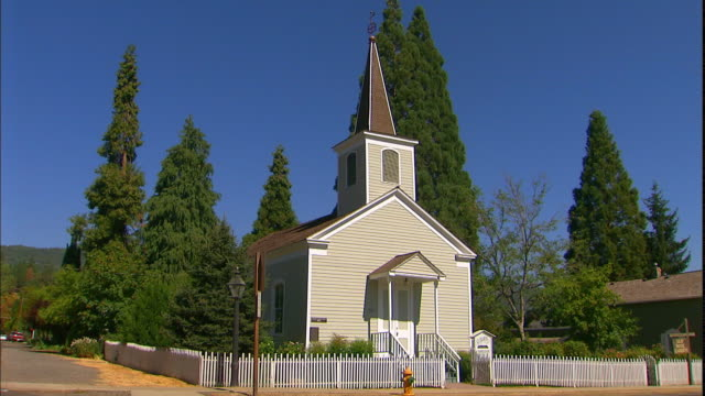 a white picket fence surrounds a church in a small town. - picket fence stock videos & royalty-free footage