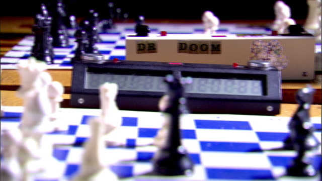 stockvideo's en b-roll-footage met white pieces king rook on back board w/ captured black pieces sitting on table male arm moving top edge of frame - schaakstuk