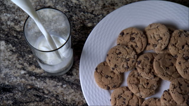 White plate w/ a dozen chocolate chip cookies empty glass on counter top stream of milk pouring into glass from off frame filling to the top Baking...