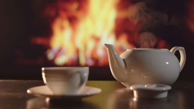 white porcelain teapot infront of a fireplace - coffee table stock videos & royalty-free footage
