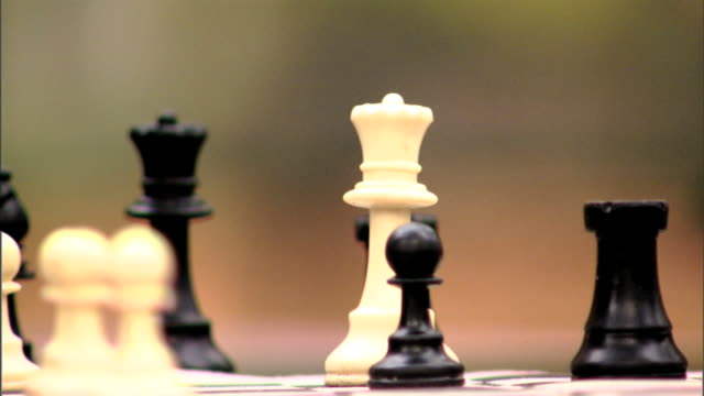 White queen game piece on board behind SOFT FOCUS Black pawns bishop knight king Caucasian male fingers lifting queen moving back near black pawn...