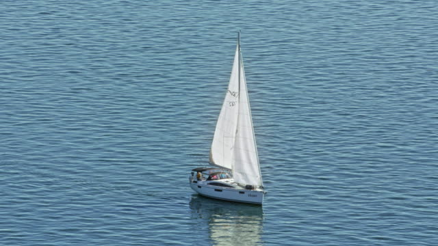 AERIAL White sailboat moving across water in sunshine