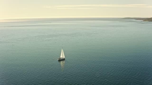 vídeos y material grabado en eventos de stock de aerial white sailboat sailing along the coast - perspectiva desde un helicóptero