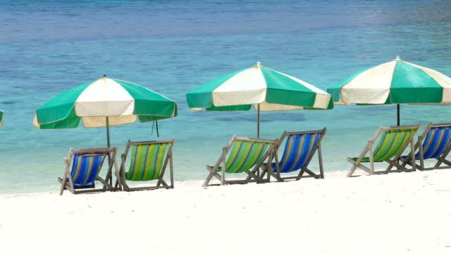 white sand beach on tropical islands in summer season - beach umbrella stock videos and b-roll footage