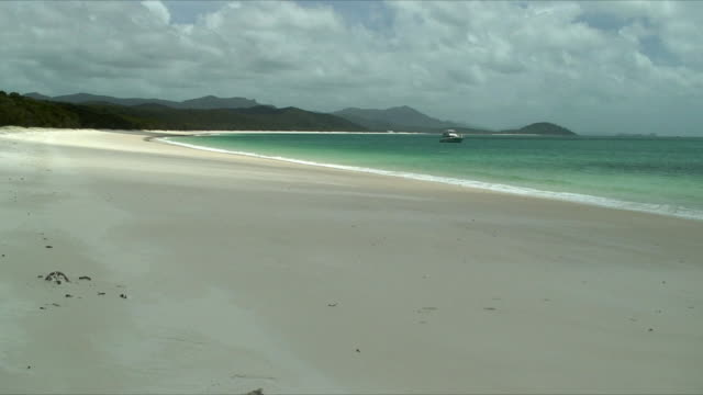 ws white sand beach under overcast sky, boat anchored in bay, whitsunday islands, queensland, australia - anchored stock videos & royalty-free footage
