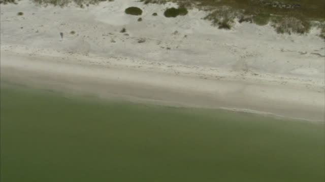 White sand beaches of Fort De Soto State Park island moving parallel to shore over Gulf of Mexico few people on beach TU XWS Barrier islands and Gulf...