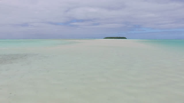 white sandbar in the middle of a lagoon with an island - tahitian culture stock videos & royalty-free footage