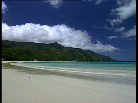 White sandy beach with gentle turquoise sea and green island mountains in background pan left to tourists walking on beach with large white fluffy clouds in blue sky Mahe Island