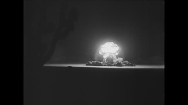White screen fades to show mushroom cloud after Abomb detonation in Nevada desert during Operation Teapot / helicopters descend onto testing site in...