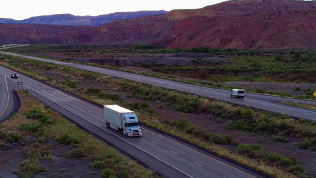 white semi-truck on interstate 70 cutting through utah landscape - autostrada interstatale americana video stock e b–roll