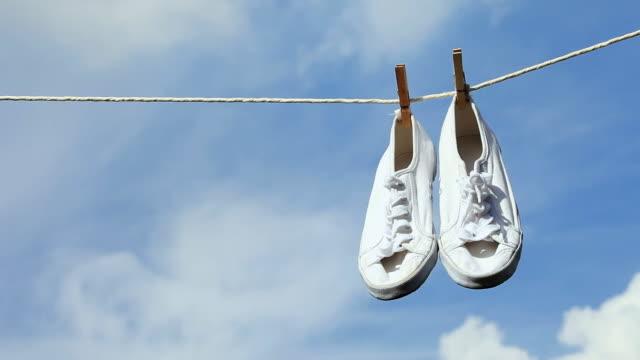 stockvideo's en b-roll-footage met cu white shoes hanging on laundry line / seoul, south korea - wasknijper