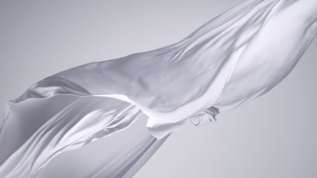white silky fabric flowing by wind in grey background, slow motion - abstract stock videos & royalty-free footage