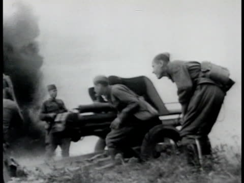 stockvideo's en b-roll-footage met white smoke explosions in field w/ distant tanks la soviet russian soldiers firing field artillery officers ducking down in trench ground shifts... - 1942